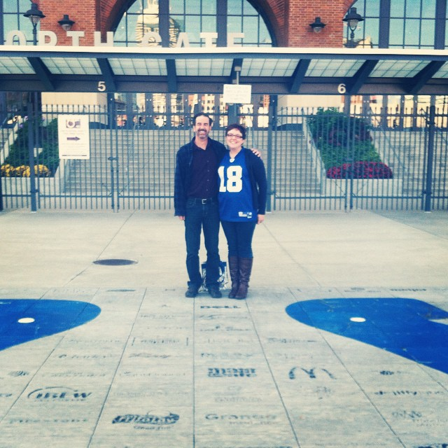 Two people standing in-front of a football stadium.